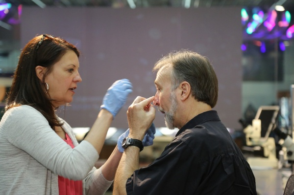 Julie Urban helping Frank Stasio superglue his face to collect face mites.