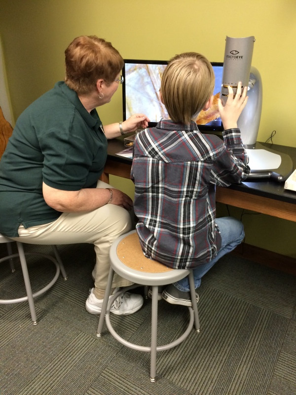 Volunteer Alice Garner helping visitor with Microeye scope, Whiteville Branch.