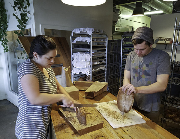 Erin and Joshua slicing bread.